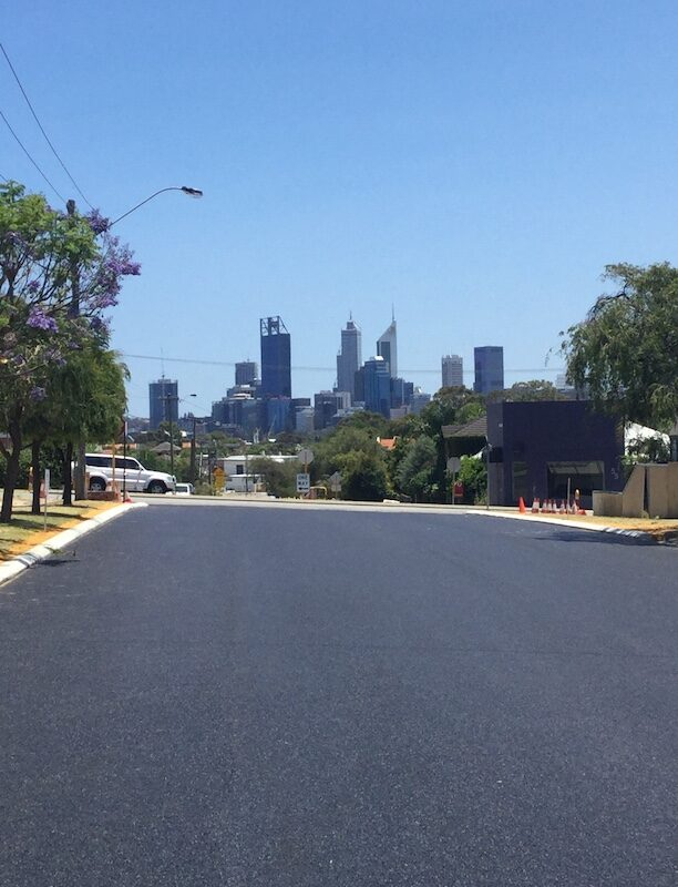 brand new road with no lines with the view of Perth city in the background